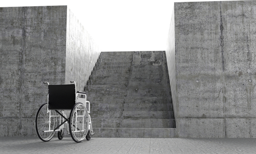 Image of wheelchair in front of barrier via shutterstock.com