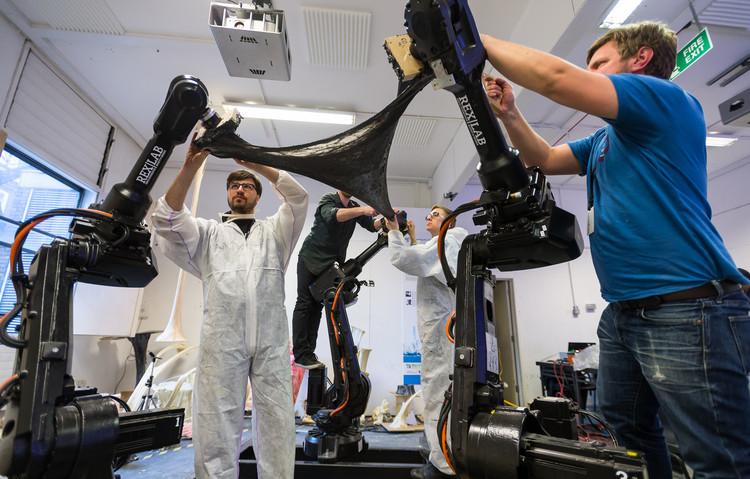 Practice 2.0: 10 Anos de Smart Geometry, Membros do grupo RoboticFOAMing liberam uma coluna de espuma modelada por três robots. Foto cortesia de Bentley
