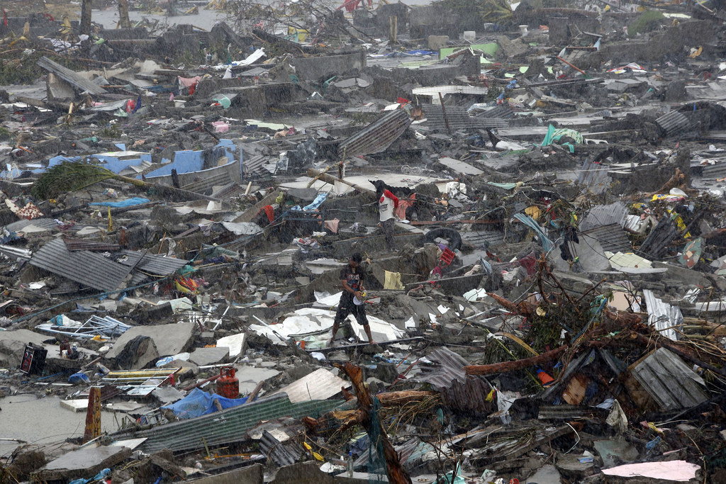 Architects & AIA Respond to Devastation in the Philippines, Call for Immediate Help, A man stands atop debris as residents salvage belongings from the ruins of their houses after Typhoon Haiyan battered Tacloban city in central Philippines November 10, 2013. Image Courtesy of Flickr user, mansunides