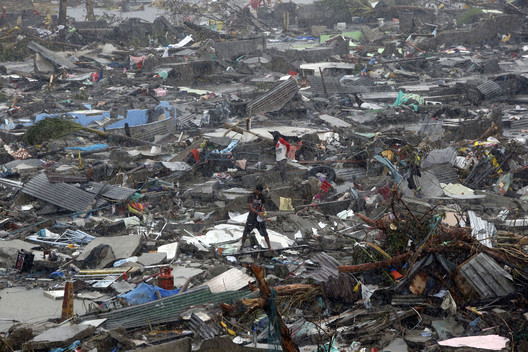 A man stands atop debris as residents salvage belongings from the ruins of their houses after Typhoon Haiyan battered Tacloban city in central Philippines November 10, 2013. Image Courtesy of Flickr user, mansunides