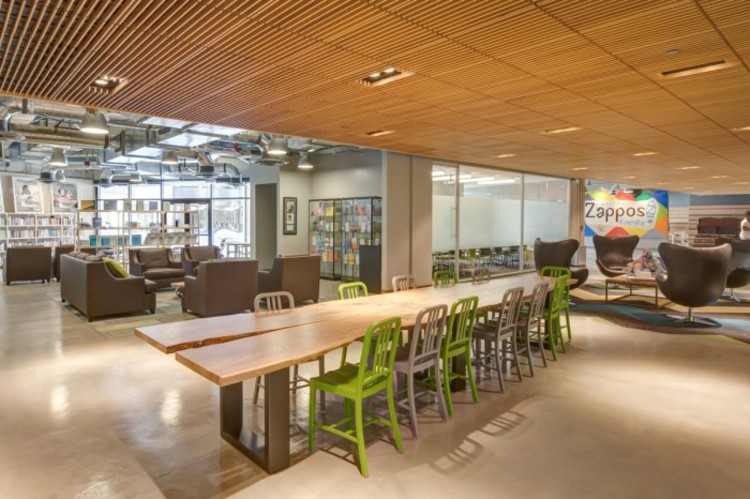 The Indicator: Poderiam os escritórios de arquitetura abolir suas hierarquias?, Zappos é uma das maiores companhias cujo funcionamento se baseia em princípios da 'holocracy' (sem uma hierarquia de equipe fixa). Sua sede em Las Vegas utiliza mobiliário coletivo para potencializar a colaboração da equipe (de acordo com a Business Insider, 'mesas são ligadas mas podem ser facilmente desconectadas ou movidas, as paredes são móveis também. Então se uma equipe precisa trabalhar de forma diferente, ou uma nova equipe é formada, o espaço pode ser alterado, e modificado novamente até que funcione'). Imagem Cortesia de Zappos, via OfficeSnapshots.com