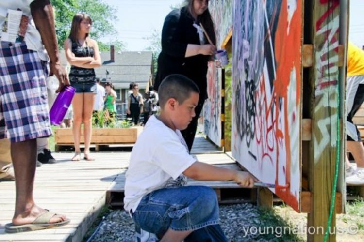 Detroit: mais leve, mais rápido e mais barato. A regeneração de uma cidade [parte I],  Um jovem de Detroit participa da criação de um mural no Projeto Beco, no sudoeste da cidade.. Image © Erik Howard