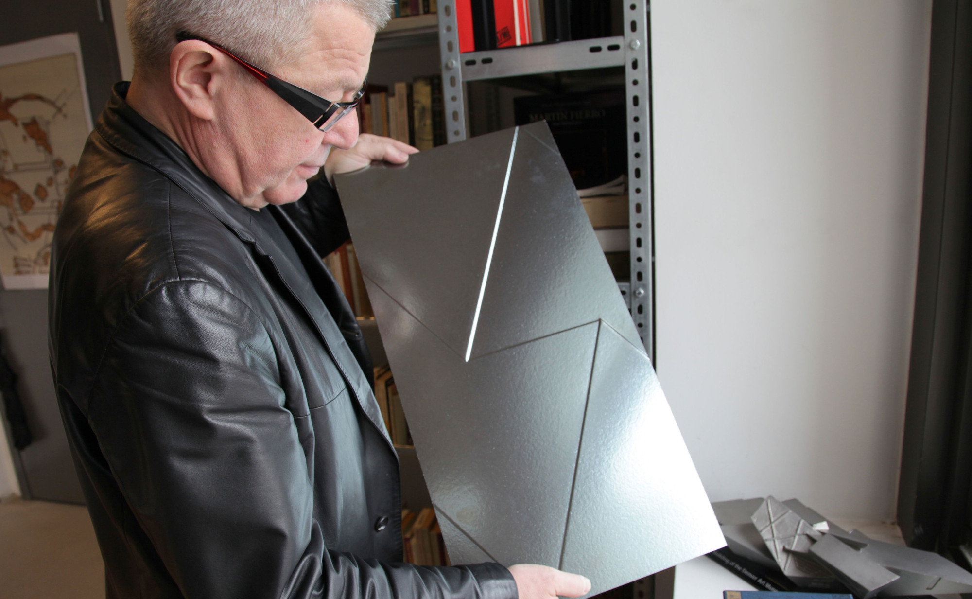 Daniel Libeskind on Italy, Design, & the State of Architecture Today, Daniel Libeskind in his New York office, holding up a panel of eco-friendly ceramic tiles the architect designed.. Image Courtesy of Lana Barkin
