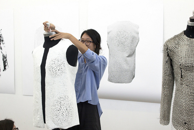 "Material Studies: When Architecture Meets Fashion, "" Lillian Lin had no fewer than six steps for turning artist's gel into the skin of her jacket. She colored the clear gel with fabric paint, spread it on a sheet, scored lines on the surface, dried it, wove the gel into strips, then ironed them flat before shaping her front, back and sleeve pieces"". Image Courtesy of University of South California Flickr Page"