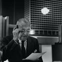 Mies, usando óculos e lendo, com modelo do novo edifício IBM ao fundo. 1969–71. Imagem Cortesia de Chicago History Museum