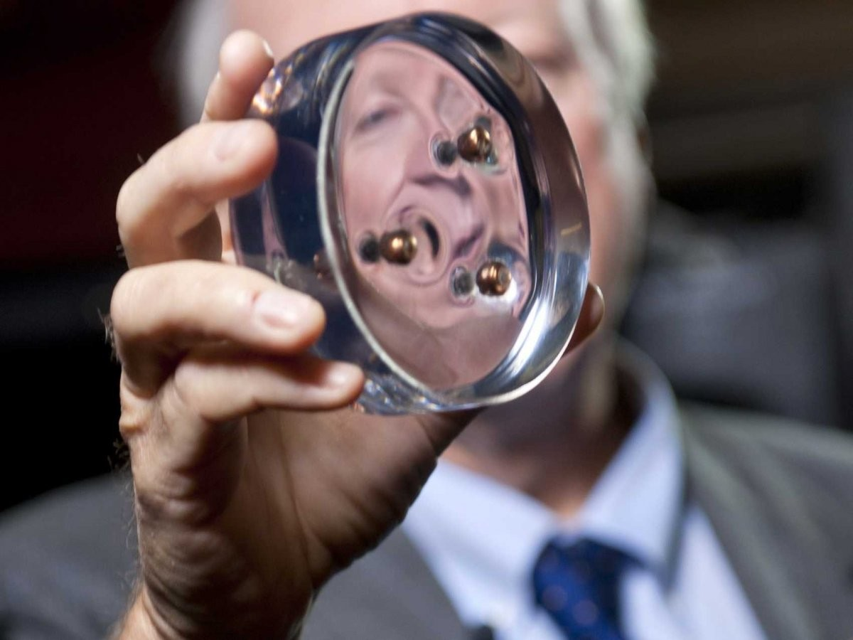 "Six ""Miracle"" Materials That Will Change Their Industries , Ned Thomas, dean of the George R. Brown School of Engineering at Rice and a materials scientist, holds a polyurethane disk with the bullets it stopped and sealed inside. Image Courtesy of Tommy LaVergne"