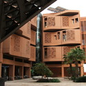 A public courtyard framed by student dormitories for Masdar Institute. Terracotta walls regulate solar heat gain, incorporating screens and shaded, exterior porches. Image © Tyler Caine