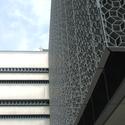 Enquanto a proteção de metal é utilizada para filtrar a luz solar, os painéis de parede cheios de ar foram projetadas para reduzir a massa térmica do invólucro exterior de um edifício e refletem a luz. Imagem © Tyler Caine