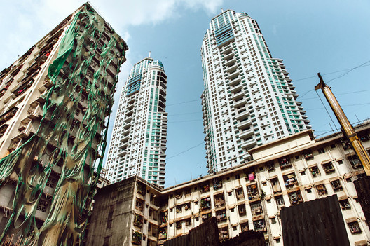 On what used to be a shantytown, Hafeez Contractor's the Imperial Towers now loom over low-income apartments. Image © Mahesh Shantaram for The New York Times