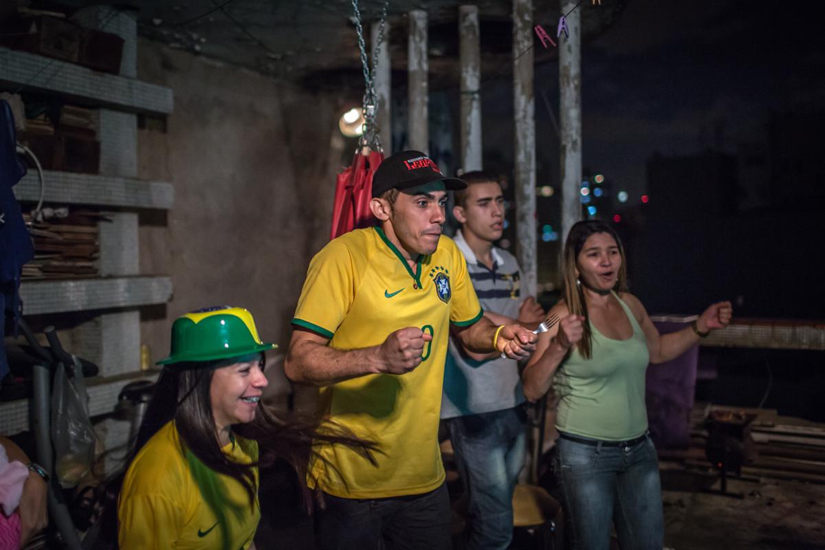 """Ensayo Fotográfico """"Copa Ocupada #01"""", por Leandro Moraes, Mauricio y su familia en la azotea celebrando el primer partido de la Selección Nacional de Brasil en la Copa Mundial de la FIFA. Imagen © Leandro Moraes"""