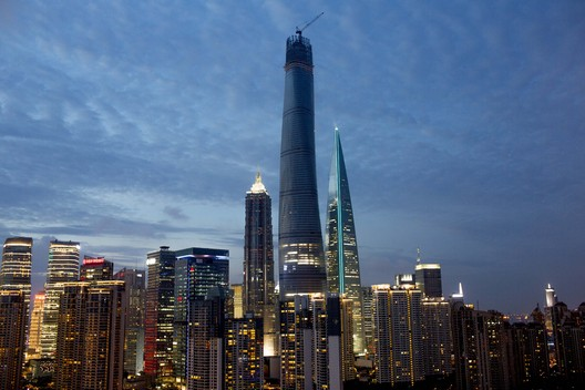 Climbing skyward, Shanghai Tower (center) is seen in Shanghai (July 2014), in the final stage of construction. Situated in Shanghai's fast-growing Pudong District, Shanghai Tower is located adjacent to the Jin Mao Tower (left) and the Shanghai World Financial Center (right). Image © Nick Almasy Photography
