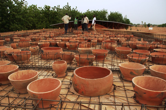 5024163828ba0d4e9a0000a2_in-progress_school-library-gando-kere-architecture_5_installing_the_pots_on_the_roof_of_the_library