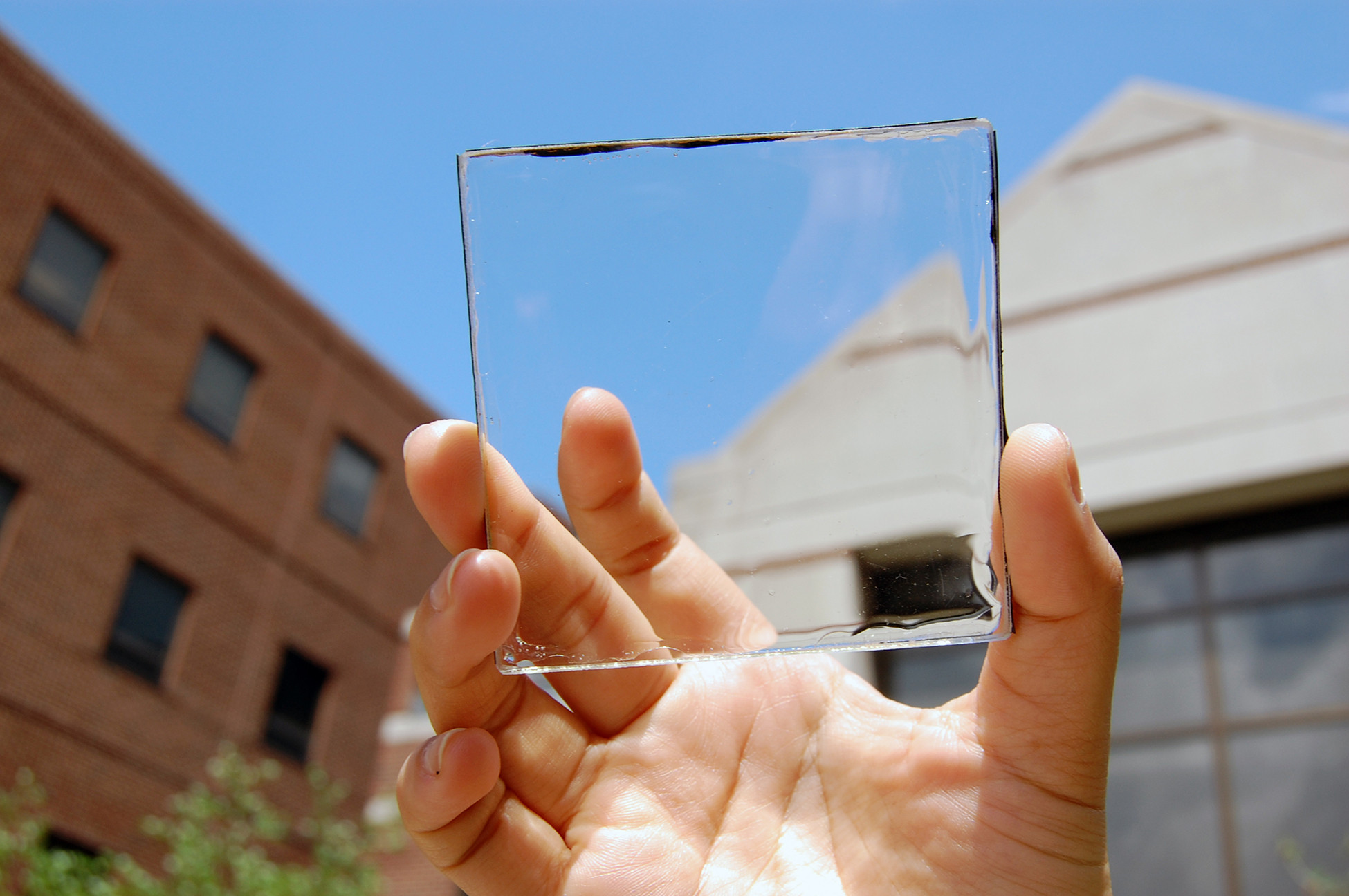Invisible Solar Harvesting Technology Becomes Reality, Solar power with a view: MSU doctoral student Yimu Zhao holds up a transparent luminescent solar concentrator module. Image © Yimu Zhao
