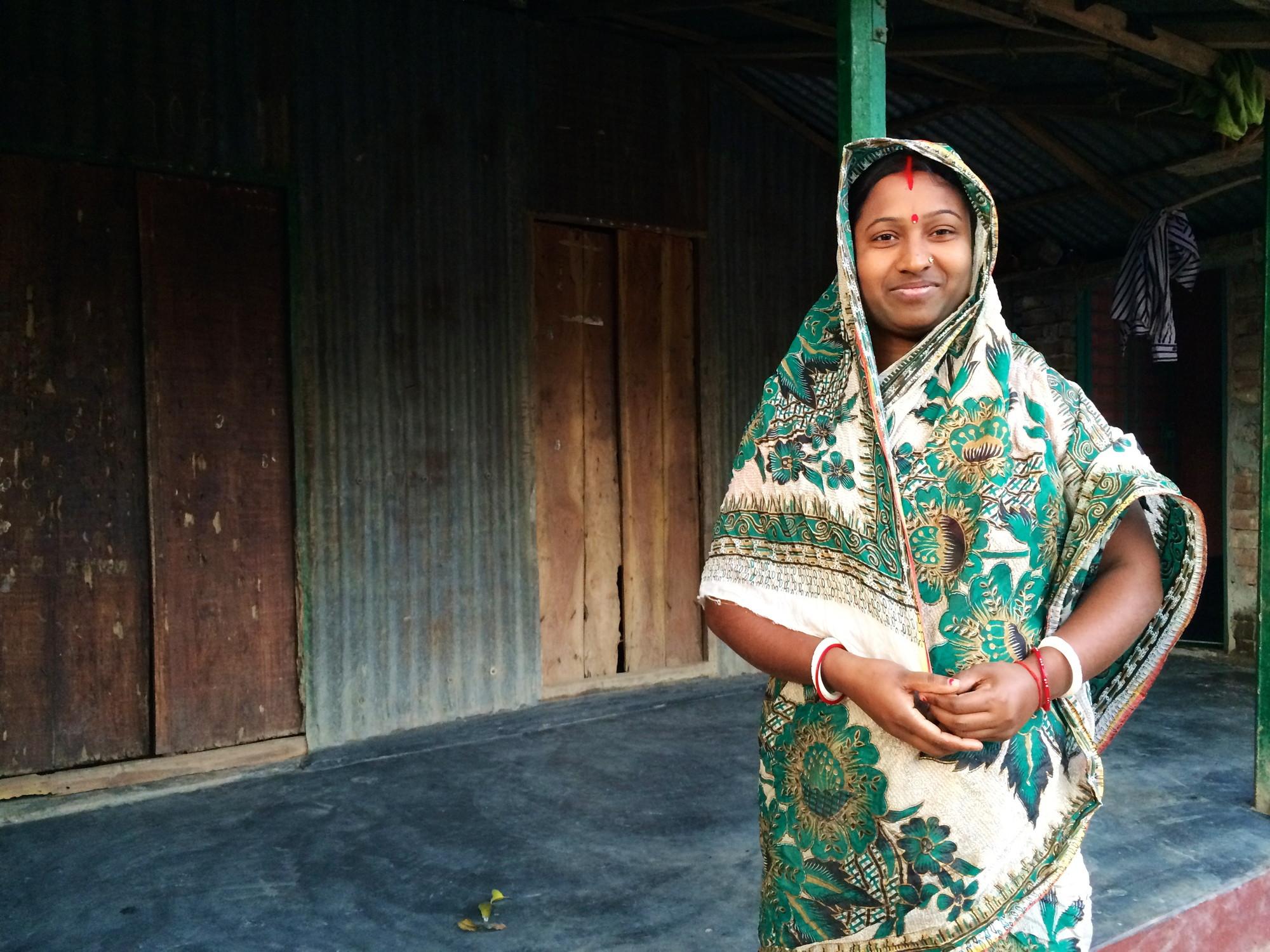 ARCHIVE Global se propone construir hogares más saludables en Bangladesh, Una mujer en la villa de Savar, Bangladesh, de pie frente al nuevo piso de radier de su familia. ARCHIVE, asociado con ADESH, insttación en Febrero 2014. Imágen cortesía de ARCHIVE Global