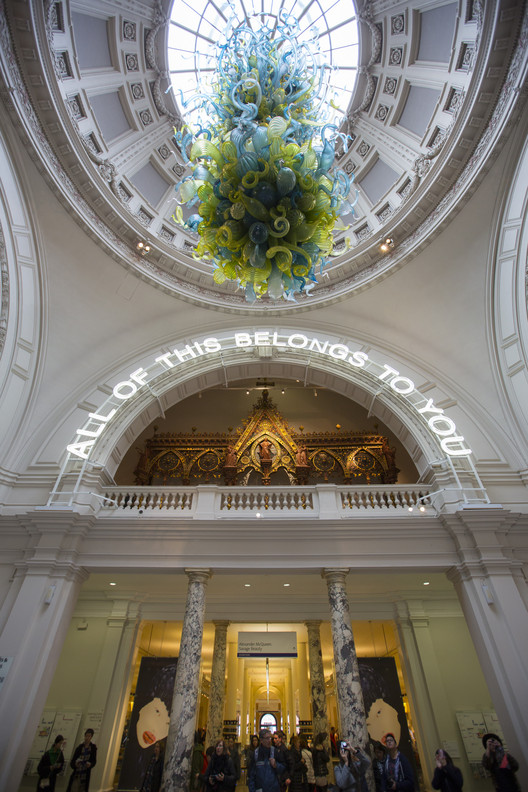 A neon sign in the V&A's grand entrance introduces the 'All of This Belongs to You' exhibition. Image © Peter Kelleher / Victoria & Albert Museum
