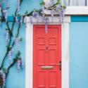 Glicinas cuelgan sobre la puerta de entrada de color rojo brillante. Imagen cortesía de Airbnb