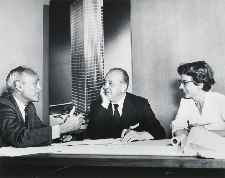 20 curiosidades sobre Mies van der Rohe, Philip Johnson, Ludwig Mies van der Rohe, y Phyllis Lambert frente a una imagen de la Torre Seagram, Nueva York, 1955. Impresión, 7½ × 9⅜ in. Fotógrafo desconocido. Fonds Phyllis Lambert, Canadian Centre for Architecture, Montreal. Imagen © United Press International