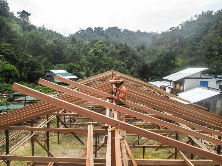 The Soul of a Community: How a Young Architect Helped Resurrect a Village Longhouse in Borneo, Construction of the split roof beside closed roof by the chief carpenter. Image © Josh Wallace