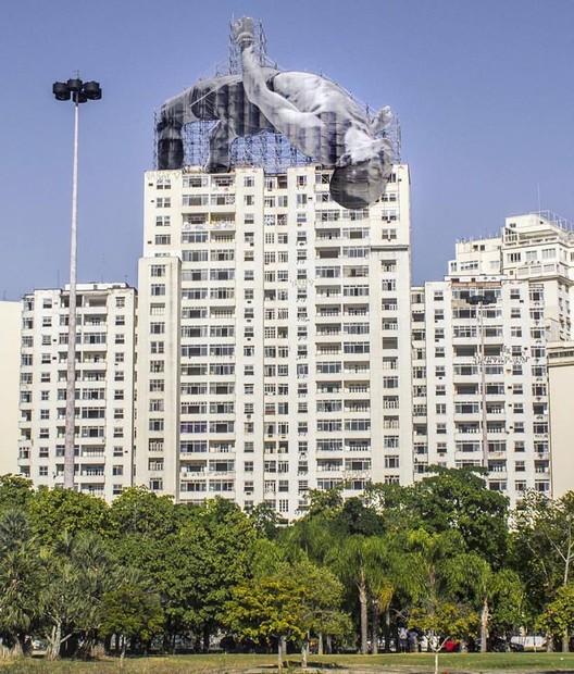 JR crea instalaciones de arte en diferentes lugares de Río de Janeiro, Imagen de Mohamed Younes Idriss saltando sobre edifício. Imagen © JR, vía Facebook del artista