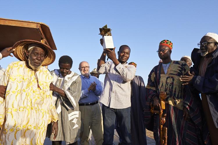 Chamada de projetos para o 5° LafargeHolcim Awards, Francis Kéré apresenta o troféu Global Holcim Awards Gold 2012 para a comunidade de Gando. Fonte: LafargeHolcim Foundation, 2012