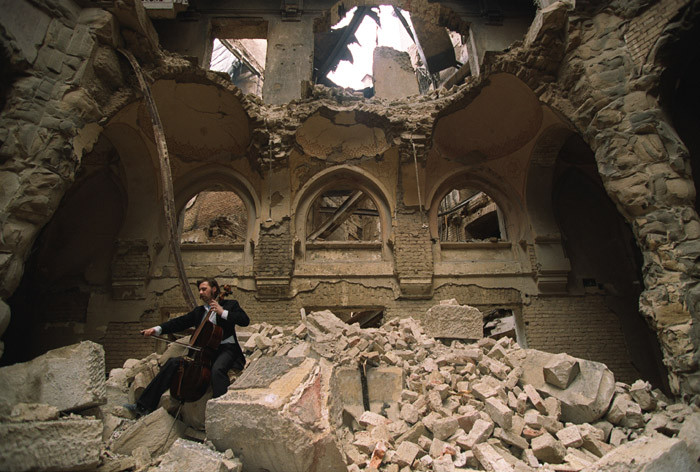 La destrucción de Barcelona, El violonchelista Vedran Smailović toca en las ruinas de la Biblioteca Nacional de Sarajevo (1992). Image © Mikhail Evstafiev [Wikipedia], bajo licencia CC BY-SA 3.0