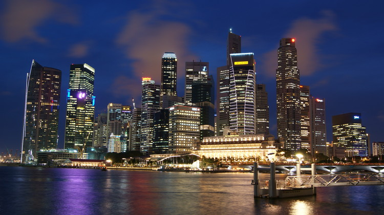How Photography Helped to Dehumanize Our Cities, Singapore skyline at night. Image <a href='https://commons.wikimedia.org/wiki/File:Singapore_Skyline_at_Night_with_Blue_Sky.JPG'>via Wikimedia</a> (public domain image taken by Wikimedia user Merlion444)