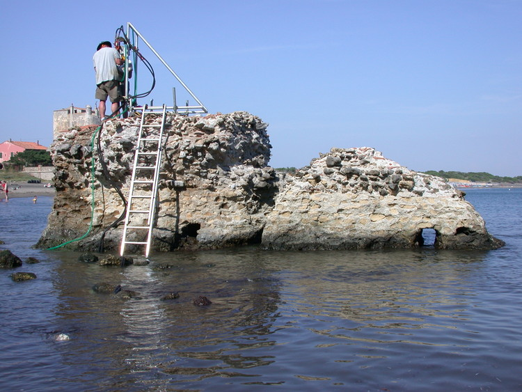 Scientists Uncover the Chemical Secret Behind Roman Self-Healing Underwater Concrete, Drilling at a ancient Roman marine structure in Portus Cosanus, Tuscany, 2003. Drilling is by permission of the Soprintendenza Archeologia per la Toscana.. Image © J. P. Oleson