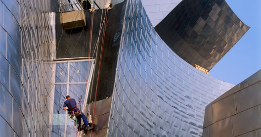Mountain climber installing titanium facade panels during the construction of the Guggenheim Museum Bilbao. Photo: Aitor Ortiz. Image © 2017 FMGB Guggenheim Bilbao