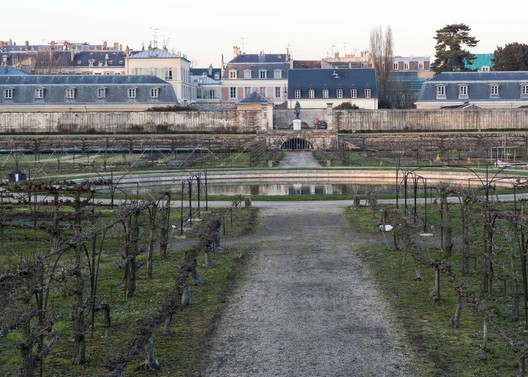 France, Potager du Roi. View across the central fountain in the Grand Carré towards the north, with a statue of Jean-Baptiste de La Quintinie and the cityscape beyond, 2015. Alexandre Petzold/World Monuments Fund