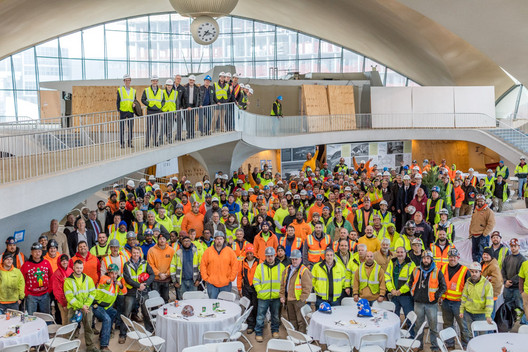Workers and partners fill the Saarinen terminal building at the topping out event. Image © Max Touhey