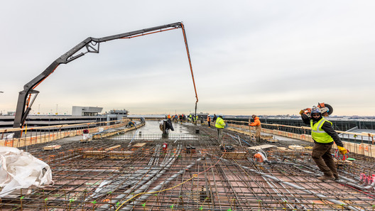 Workers pour concrete on top floor of north hotel structure. Image © Max Touhey