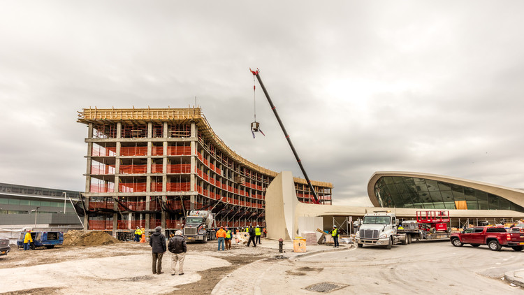 Hotel Transformation of Saarinen's TWA Terminal Tops Out, TWA Hotel flag and American Flag raised to the top of the north hotel structure. Image © Max Touhey