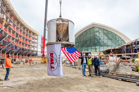 MCR CEO Tyler Morse and Turner Construction's Rick Faustini and Gary McAssey standing next to the north hotel tower crane with ceremonial flags. Image © Max Touhey