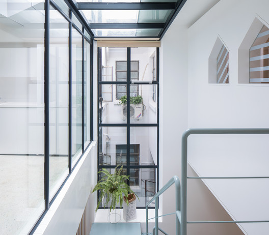 Open up part of the roof to create a large skylight which brings in lots of natural light to the middle part of the space.. Image © Tian Fangfang