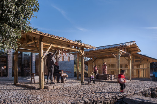 The wooden canopies applied as a bamboo shoot squeezing space and a pavilion . Image © Meng Zhou