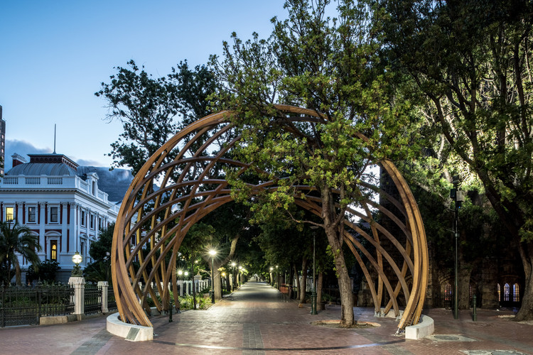 Snøhetta and Local Studio Unveil Wooden Archway Honoring Archbishop Desmond Tutu in South Africa, Sited between South Africa's National Parliament and St. George's Cathedral, the seat of the Archbishop of Cape Town, the Arch frames the public entrance to a landscaped promenade known as the Company's Garden, which boasts many of the city's cultural institutions. Image © David Southwood