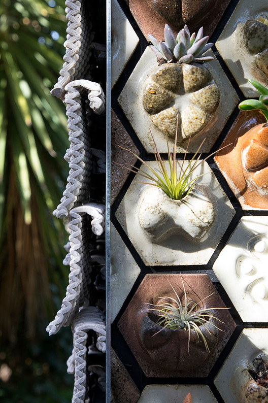 """A corner detail shows 3D-printed ceramic """"seed stitch"""" tiles overlapping on the facade corner. The """"planter tiles,"""" which hold succulents and air plants, face forward. Image © Matthew Millman"""
