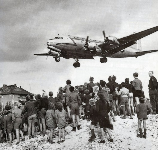 Children watch an American plane land with supplies at Tempelhof Airport during the Berlin Airlift. Image© <a href='https://commons.wikimedia.org/wiki/File:C-54landingattemplehof.jpg'>United States Air Force Historical Research Agency</a></noindex></noindex> licensed under <noindex><noindex><a target=