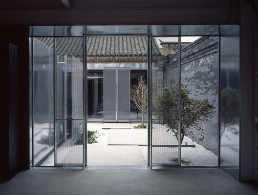 view from exhibition space to office through courtyard. Image © Hao Chen