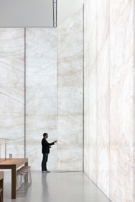Apple Store, Sands Cotai Central, Macau - interior retail space with glass-stone composite curtain wall with person. Image Courtesy of Nigel Young, Foster + Partners