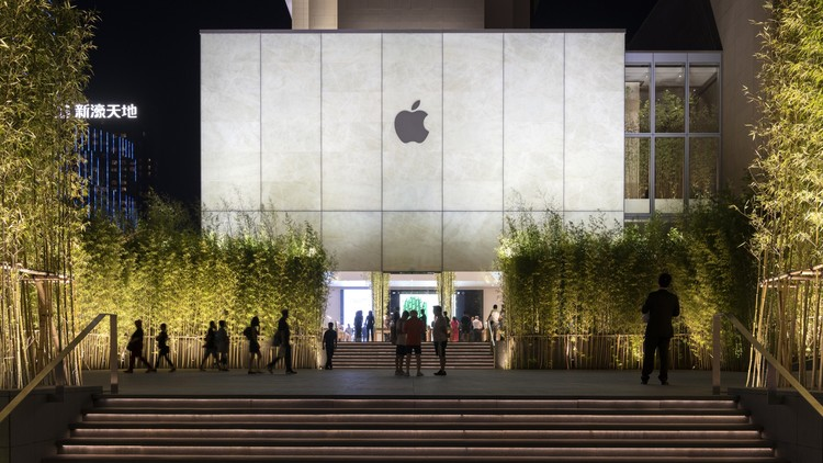 Stone, Glass, and Bamboo Meet in Foster + Partners' Recently-Opened Apple Store in Macau, Apple Store, Sands Cotai Central, Macau - exterior at night with the cube illuminated and bamboo planting framing the entrance with people. Image Courtesy of Nigel Young, Foster + Partners
