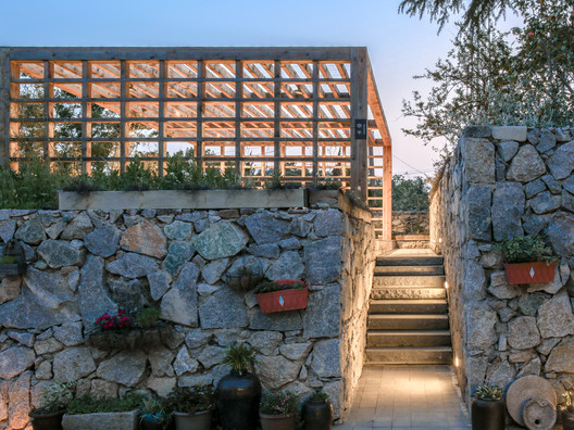 Small stone path and wooden fence dining area. Image © Kun Zhang