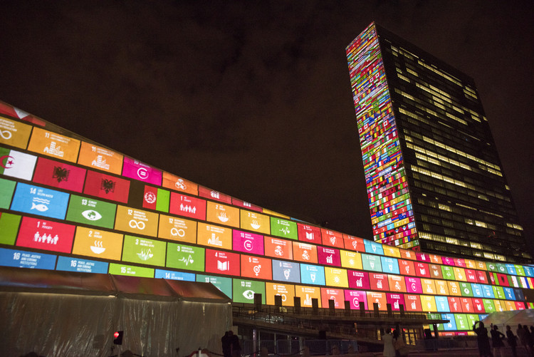 """Las ciudades necesitan acelerar el cumplimiento de la Agenda 2030, advierte ONU-Habitat, © <a href=https://www.flickr.com/photos/un_photo/'>United Nations Photo [Flickr]</a>, bajo licencia <a href=""""https://creativecommons.org/licenses/by-nc-nd/2.0/"""">CC BY-NC-ND 2.0</a>. ImageProyección de los Objetivos de Desarrollo Sostenible (ODS) en la fachada de las oficinas centrales de la ONU en Nueva York, 2015."""