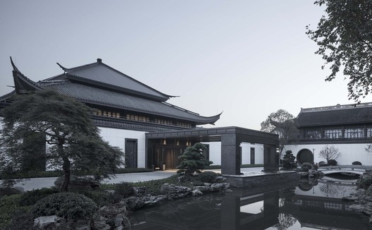 The wrapped edge in the Chinese-style tile part of roof covering at the lower eave of new lobby works in concert with the old lobby; lattice windows refine the traditional architectural elements of Shaoxing. Image © Qiang Zhao
