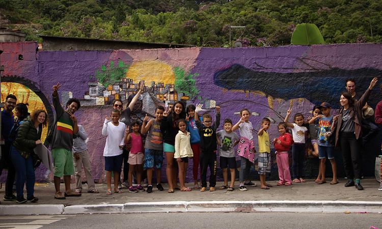 Legibilidade cidadã e engajamento comunitário: o projeto Passeia, Jardim Nakamura, Registro da caminhada exploratória realizada ao longo do território. No muro, uma das intervenções visuais realizadas. Registro: Fluxo imagens. Image Cortesia de COURB Brasil