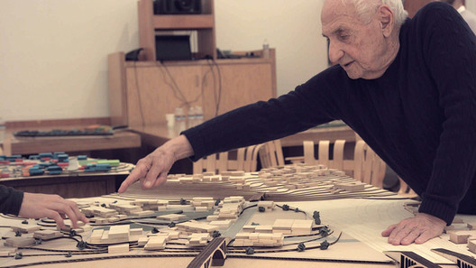 Frank Gehry and a student model from one of his studios on prison design. Image © Frank Gehry: Building Justice