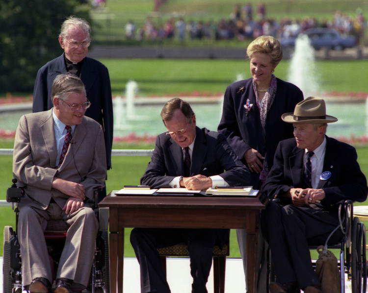 President Bush signing the 1990 Americans with Disabilities Act. Image © Reuters