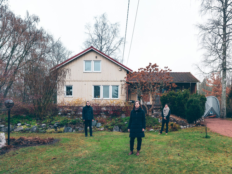 Finnish–American Trio to Curate the Pavilion of Finland for the 2020 Venice Biennale , New Standards curatorial team Kristo Vesikansa (left), Laura Berger and Philip Tidwell in front of a Puutalo house in the Jollas district of Helsinki. Photo Juuso Westerlund. Image Courtesy of Archinfo Finland