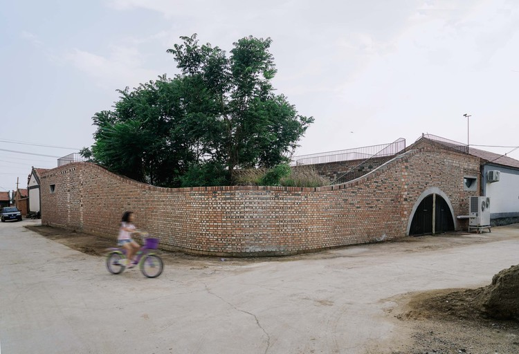 Окруженные новой стеной, пышные старые деревья и черепичные крыши старых домов по-прежнему являются повседневным пейзажем в деревне сегодня.  Изображение © Юмэн Чжу