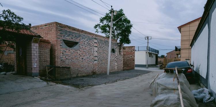 Южный фасад дома не выделяется среди коттеджей такой формы.  Изображение © Юмэн Чжу